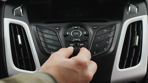 Male hand adjust the volume or the tuning of the car radio Footage