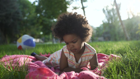 Close up of african-american girl lies in the park on the bedspread and watches GIF