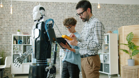 Young people working with robot in office testing response with control ビデオ