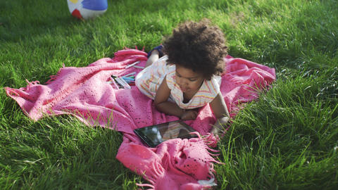 Little african-american girl is watching cartoons on tablet in park GIF