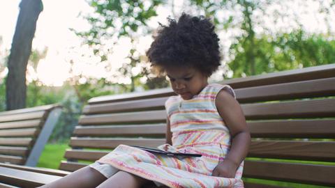 Displeased african-american girl is watching cartoons on tablet in park GIF