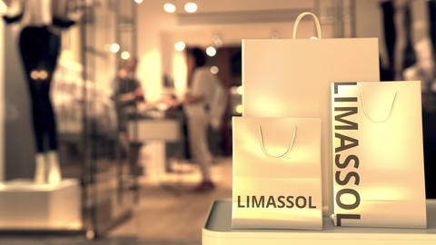 Paper shopping bags with LIMASSOL text against blurred store. Cypriot shopping GIF