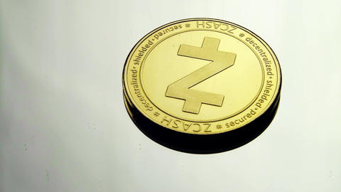 Z-cash gold coin spins on a white mirror surface slightly slowed down 01 Live Action