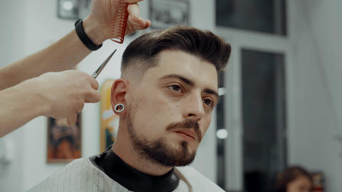 Male Barber Giving Client Haircut In BarberShop ビデオ