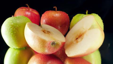 Closeup slow motion video of two halves of fresh ripe apple falling on black Archivo