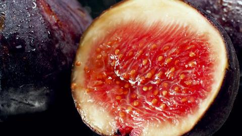 Closeup 4k video of water droplets falling on fresh ripe fig cut in half Archivo