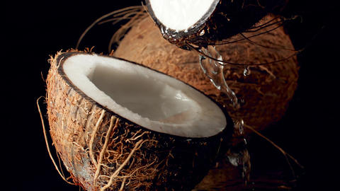 Closeup slow motion video of coconut milk slowly flowing out of broken coconut Archivo