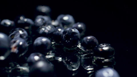 Closeup slow motion video of lots of wet blueberries falling on black background Archivo
