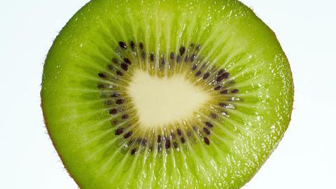 4k video of slice of kiwi fruit squeezing and exploding on white background Archivo