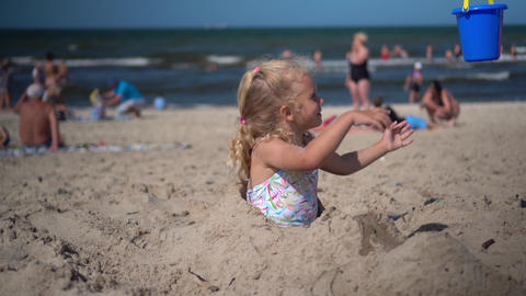 Buried little girl take toy bucket with water from mother and pour it on sand GIF