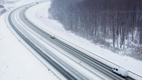 Aerial view of traffic on a road surrounded by winter forest in snowfall Footage