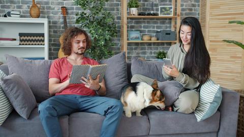 Girlfriend and boyfriend using smartphone reading book and caressing corgi dog Archivo