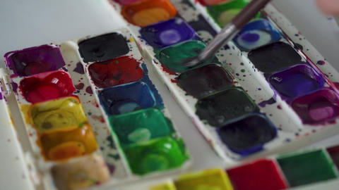 Brush takes different colors of watercolor paints from a palette and mixes them Footage