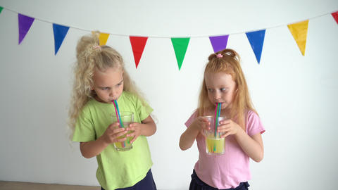 Naughty girls making bubbles in glasses of orange juice with straw GIF