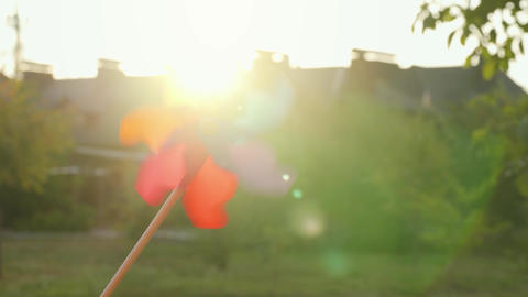 Plastic rainbow windmill rotates on the background of blurry houses and sunset Footage