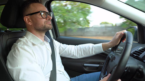 Bearded man in glasses and white shirt driving a car in... Stock Video Footage