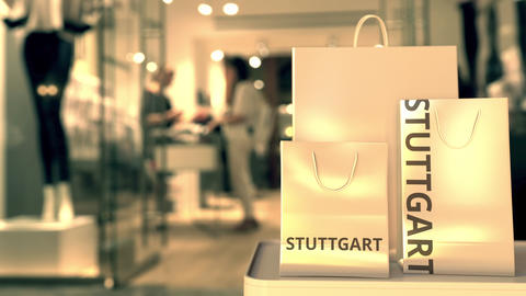 Shopping bags with STUTTGART text against blurred store. German shopping related GIF