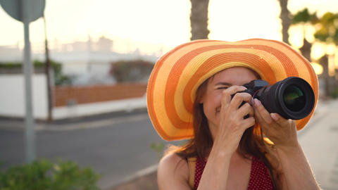 Photographer tourist woman in a big yellow hat taking photos with camera in a Footage
