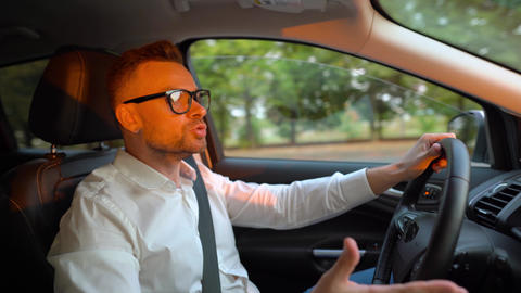 Bearded man in glasses and white shirt driving a car in sunny weather and swears Live Action
