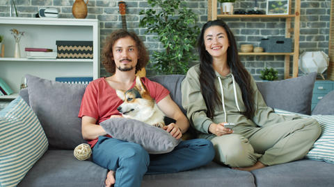 Cheerful couple watching TV at home and stroking corgi... Stock Video Footage