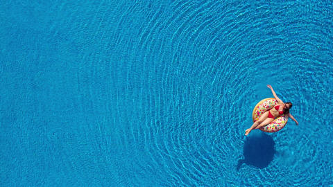 Aerial view of a woman in red bikini lying on a donut in the pool Footage
