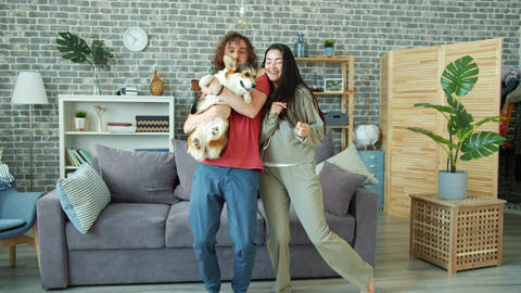 Happy couple dancing at home holding welsh corgi pembroke dog having fun Live Action