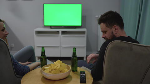 Man and woman are sitting in chairs, watching TV with a green screen, drink beer Footage