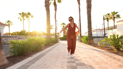 Happy woman in a big yellow hat running along a palm alley at sunset Footage