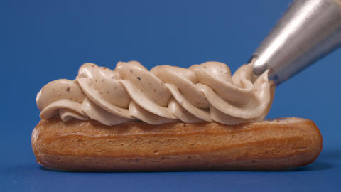 Confectioner squeezes custard from pastry bag to the eclair, cream on the cake Live Action