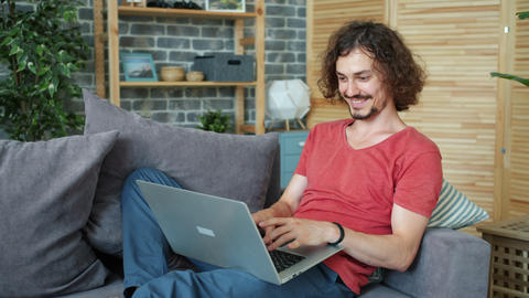 Young handsome man working with sofa typing laughing on... Stock Video Footage