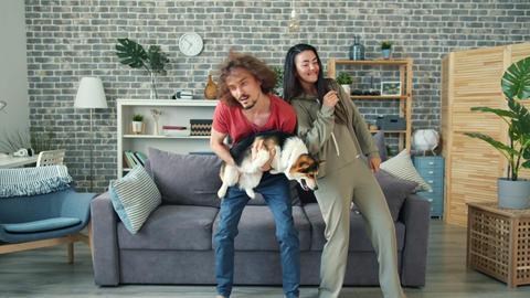 Joyful guy dancing with girlfriend holding corgi puppy having fun at home Archivo