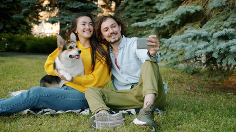 Happy couple taking selfie with corgi breed dog in city park using smartphone Archivo
