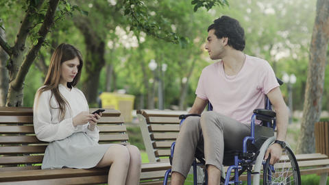 Young man in a wheelchair trys to meet woman in the park. Woman dont talk with Footage