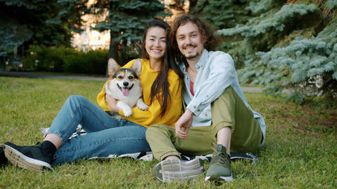 Slow motion portrait of young couple and corgi dog smiling relaxing in park Archivo