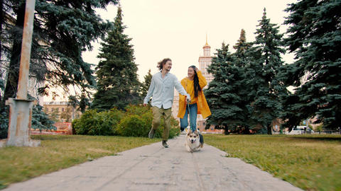 Slow motion of man and woman running outdoors with funny corgi dog having fun Archivo
