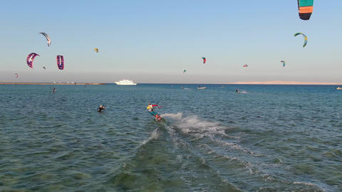 Kite surfer is gliding in the sea on high speed, camera span behind him Live Action