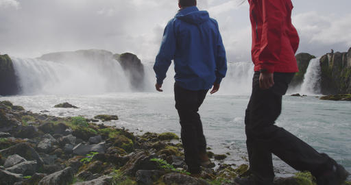 Iceland Travel Couple hiking in nature hike by Iceland waterfall Live Action