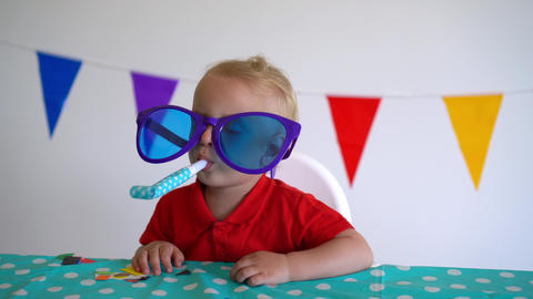 Cute boy with huge glasses and party noisemaker by birthday table. Gimbal motion Live Action