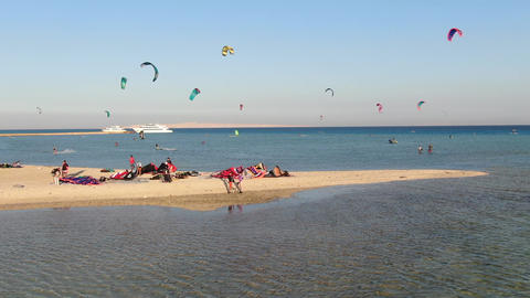 Aerial footage of a big group of people on the beach and people kitesurfing Live Action