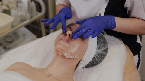 A professional beautician applies a transparent fabric face mask to the face Live Action