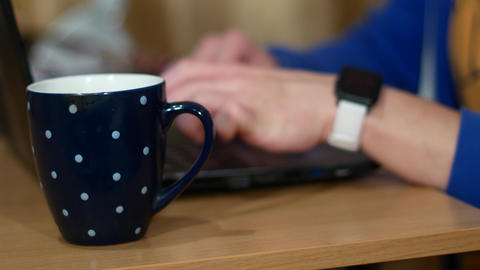 Freelancer is working on a laptop. Near a cup with a hot drink. A man drinks tea Live Action