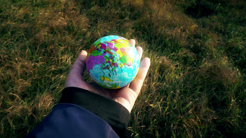 world in hand, female hand holding planet globe earth outside on grass Live Action