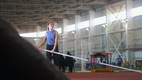 Pole vaulting in the indoors stadium - young woman with pigtails raises up the Live Action