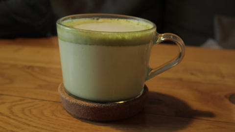Matcha Green Tea Latte in Cup at Restaurant or Cafe. Healthy Drink Live Action