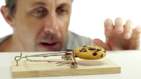 Man Looking at Cookie In Rat Trap Footage
