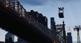 Evening Shot of Roosevelt Island Tram Next to Queensboro Bridge Footage