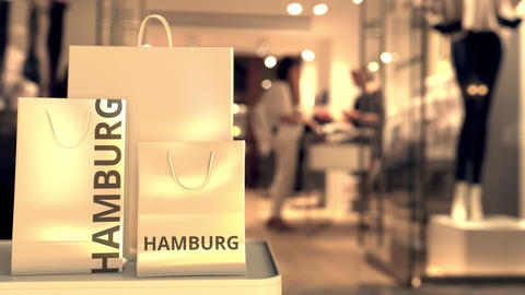 Paper shopping bags with Hamburg caption against blurred store entrance. Retail Live Action