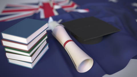 Graduation cap, books and diploma on the Australian flag. Higher education in Footage