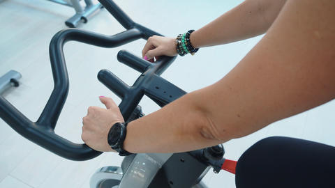 Female hands with fitness watch holding handlebar of indoor bike at cycling Live Action