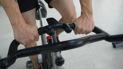 Male hands holding handle static bike in fitness club. Sportsman training gym Live Action